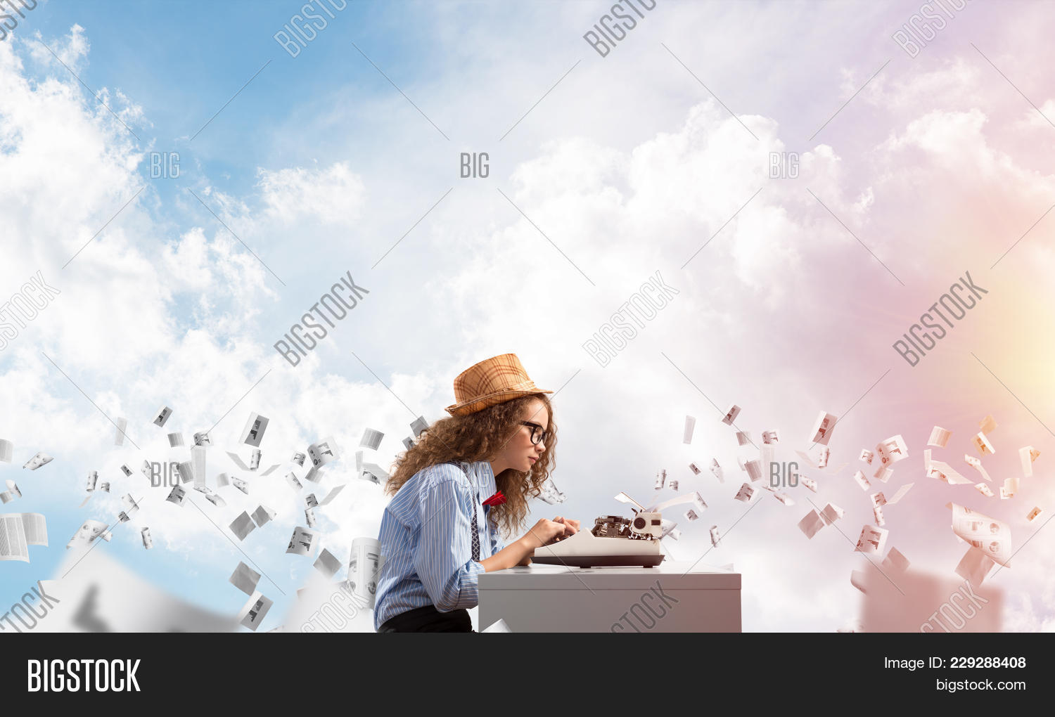 Young And Beautiful Woman Writer In Hat And Eyeglasses Using Typing Machine While Sitting At The Tab