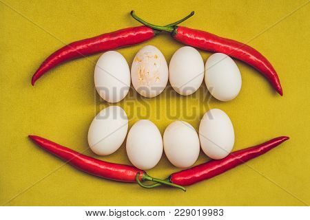 Eggs and red pepper in the form of a mouth with teeth. One of the teeth is sick in the form of a cracked egg. Sick tooth concept. stock photo