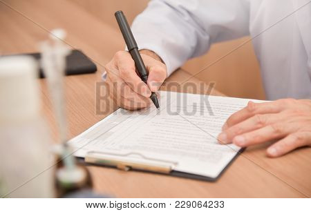 Close up on hands. Asian male doctor is writing something on clipboard, prescription, paper work,patient check list paper or application form. stock photo
