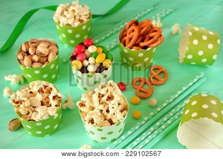 Popcorn, multicoloured drops, pretzels with salt and pistachio nuts in paper cups on green background. Snacks assortment stock photo
