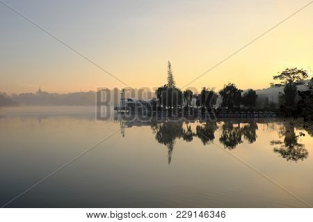 Beautiful landscapes of Da Lat city at morning with lake in fog, pine tree reflect on water, scenery in cyan, this place is romantic destination for Vietnam travel stock photo