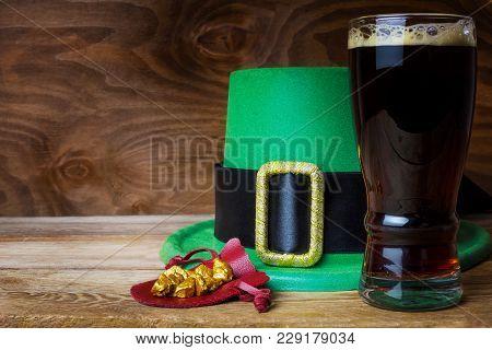 Saint Patrick day symbols green hat, leprechaun gold prills and dark beer stock photo