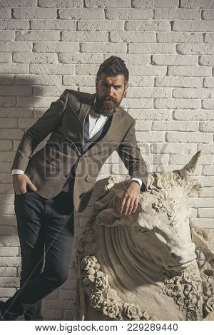 Man with beard and mustache on white brick wall background. Guy near piece of art - sculpture of bull. Hipster with strict face in suit abuts on sculpture of bull. Masculinity and brutality concept. stock photo