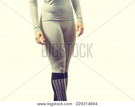 Clothing fashion sport concept. Fit female legs wearing thermoactive underwear pants trousers. Slim woman in sporty clothes stock photo
