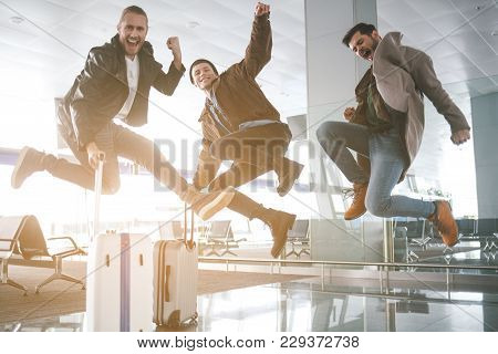 Full length portrait of beaming comrades jumping in hall. Baggages locating opposite them. Fun and journey concept stock photo
