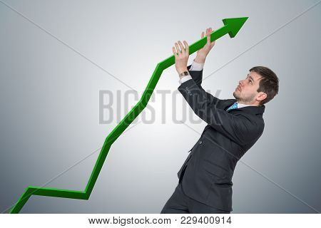 Businessman is pushing arrow in graph up. Growth and maximizing earnings concept. stock photo