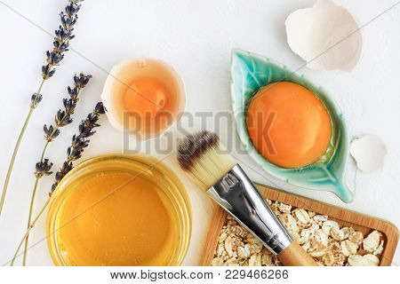 Bright egg yolks, oatflakes, honey, lavender with cosmetic brush closeup, natural holistic ingredients for homemade beauty care. Fresh products for glowing skin.  White background viewed above. stock photo
