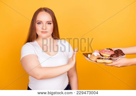 I'm against eating products containing fat! Will-powered woman wearing white tshirt is refusing to consume tasty delicious sweets on a plate, isolated on bright yellow background stock photo