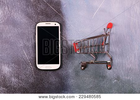 Online shopping concept, shopping cart and smart phone stock photo