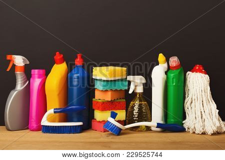 Group of colorful cleaning products on dark background. Different bottles, sponges, brushes and mop on wood table. House keeping, tidying up, spring-cleaning concept, copy space stock photo