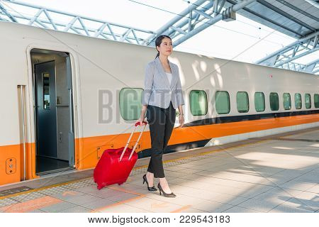 beautiful Asian girl gets off the train after the high speed rail arrived her destination station and walking on the platform. stock photo