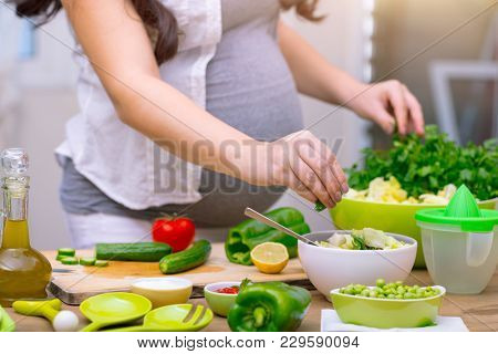 Happy pregnant woman cooking at home, doing fresh green salad, eating many different vegetables duri