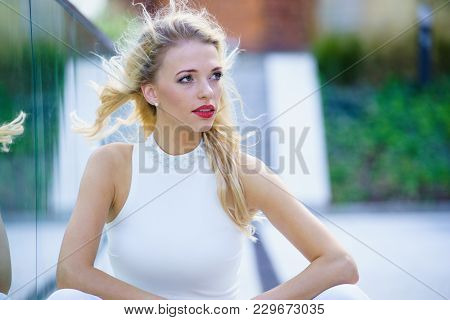 Glamurous female fashion model presenting casual elegant outfit. Woman wearing crop top and skirt. Summer urban outfit, outdoor photo session. stock photo