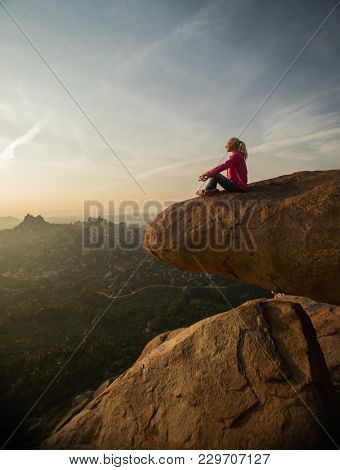Woman meditating at sunset on hilltop in hampi, india stock photo