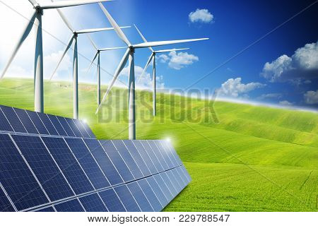 Renewable or green energy concept with solar panels and wind turbines on a green meadows stock photo