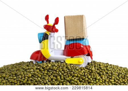Express delivery service by motorcycle.Colorful motorcycle with delivery boxes on pile mung beans on the white background with copy space for text. Mung beans is a leguminous plant native to Asia. stock photo