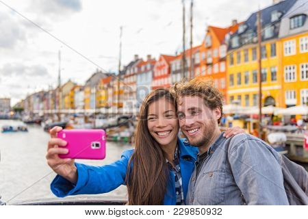 Copenhagen travel couple tourists taking selfie photo with phone camera. Smiling young people students at old port Nyhavn, tourism danish landmark in Denmark, northern Europe. stock photo