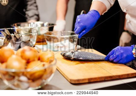 Woman cook preparing and cleaning raw dorada fish with knife on the wooden cutting board in kitchen stock photo