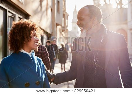 Middle Aged Couple Walking Through City In Fall Together stock photo