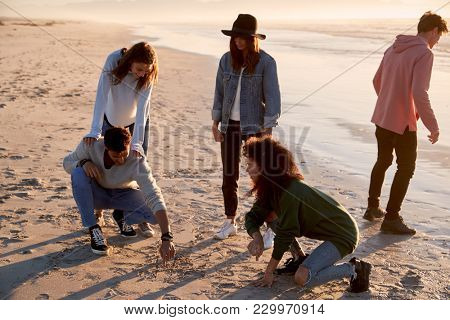 Friends Playing Noughts And Crosses In Sand On Winter Beach stock photo