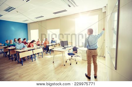 education, school, learning, teaching and people concept - teacher standing in front of students and