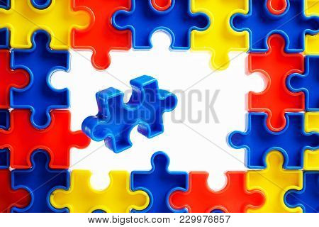 Pieces from a colorful jigsaw puzzle arranged to form a page on white background. Break barriers together for autism. stock photo