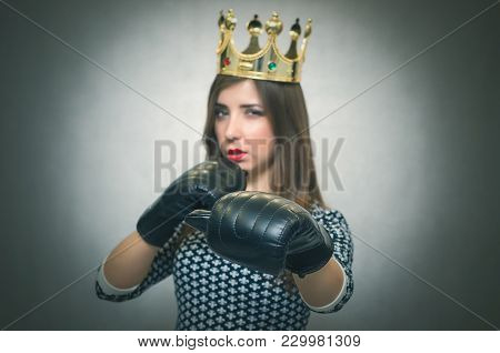 Angry confident woman with gold crown on her head and in a boxing gloves. Bossy girl in bad mood concept. Dissatisfied wife. Women Match. Women beauty contest concept. Female rivalry. stock photo
