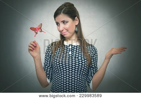 Happy merry unconcern woman holding in hand a toy red butterfly and is amazed. Innocent excited girl concept. Carefree bahavior. Dreaming girl. stock photo