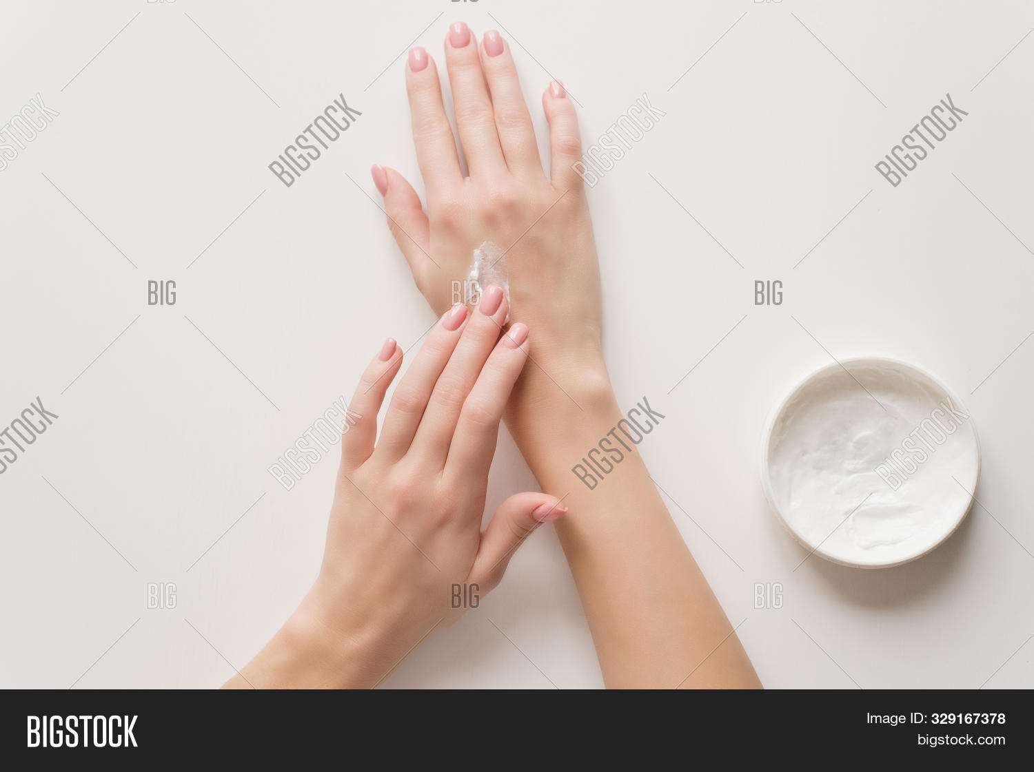 The girl distributes moisturizing cream on her hands. Hands on a white background with a jar of white cream. The concept of moisturizing, preventing skin aging.