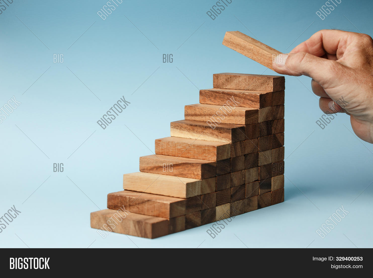Man Hand Put Wooden Blocks Arranging Stacking For Development As Step Stair, On Blue Background. Con