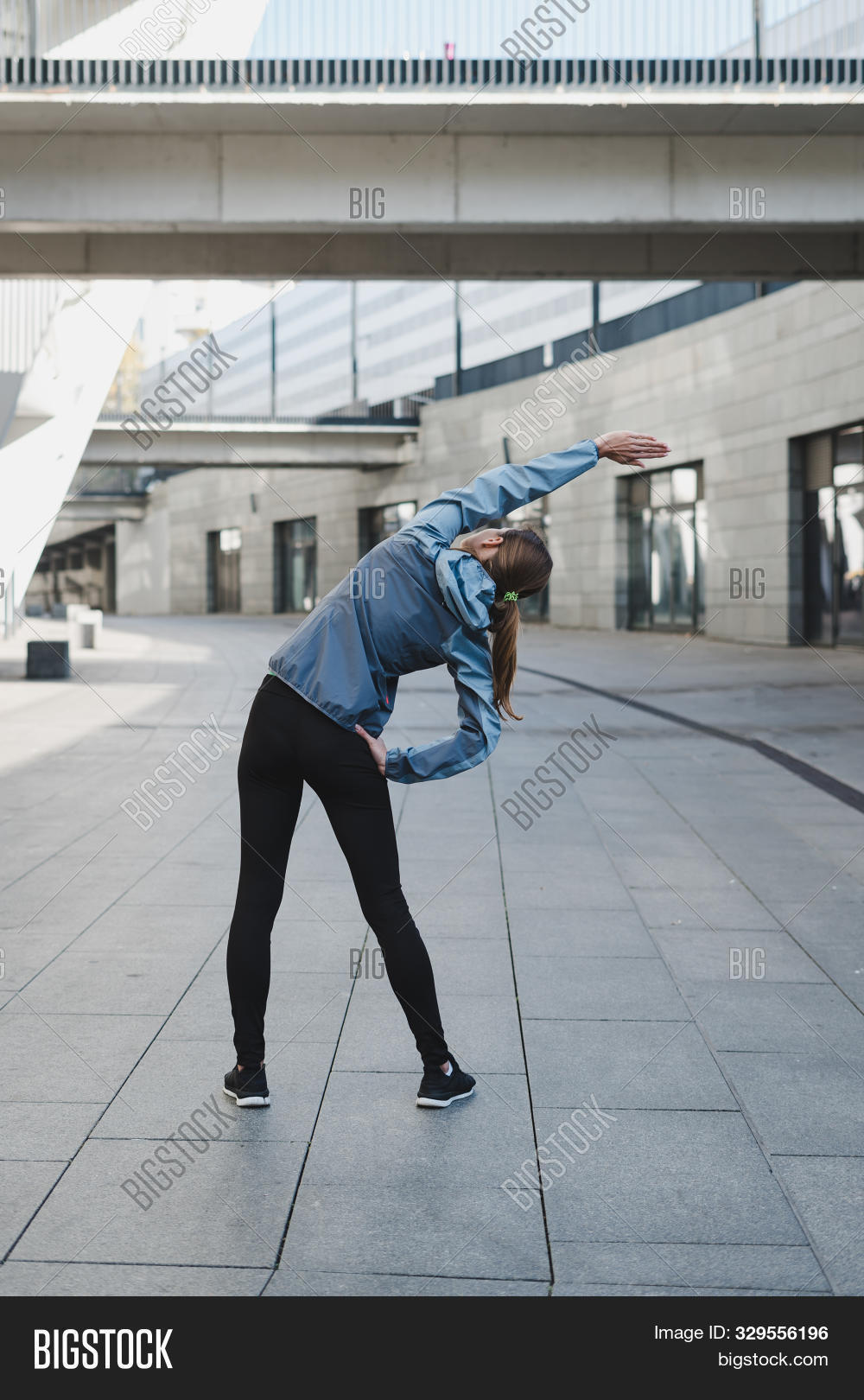 Athletic Girl Stretching Body Before Cardio Workout. Back View Of Young Adult Sportswoman In Sportsw