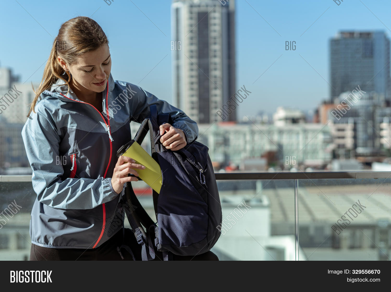 Woman packing thermos in rucksack pocket, standing against urban background with copy space. Attractive young adult girl in trendy wear clothes with backpack spending travel weekend outdoor in city