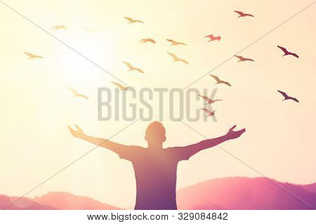 Freedom feel good and travel adventure concept. Copy space of silhouette man rising hands on sunset sky at top of mountain and bird fly abstract background. Vintage tone filter effect color style. stock photo