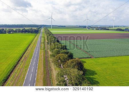 Aerial from a typical dutch landscape: straight roads, windmills and beautiful meadows in the Netherlands stock photo