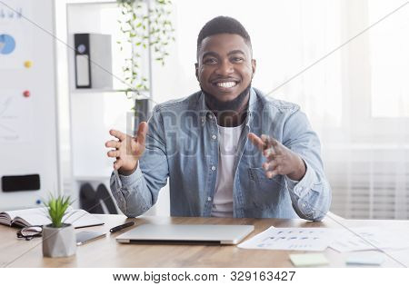 Smiling african american business coach sharing his experience and creative ideas at camera, talking about successful work strategies, copy space stock photo