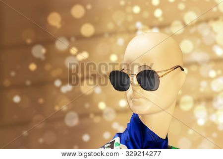 Mannequin head in sunglasses on a beige bokeh background. dummy model in a shop window of clothes and accessories, bald doll head stock photo