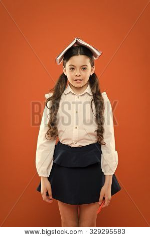 Read a ton, learning is fun. Funny small child holding book to read on her head on orange background. Adorable little girl learning to read at school. Read to succeed. stock photo
