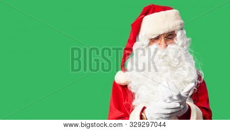 Middle age handsome man wearing Santa Claus costume and beard standing Suffering pain on hands and fingers, arthritis inflammation stock photo
