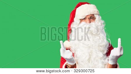 Middle age handsome man wearing Santa Claus costume and beard standing Showing middle finger doing fuck you bad expression, provocation and rude attitude. Screaming excited stock photo