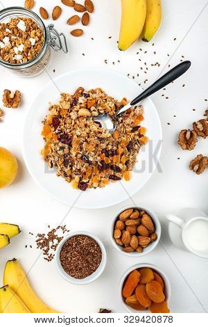 Granola muesli breakfast with with milk, dried apricots, cranberries, almonds and flax seeds in bowl on a white background. Healthy cereal breakfast stock photo