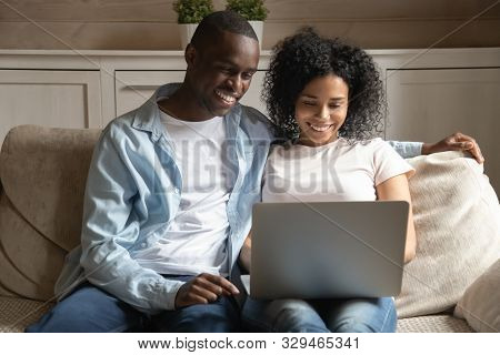 Smiling african american married spouse sitting at home with laptop. stock photo