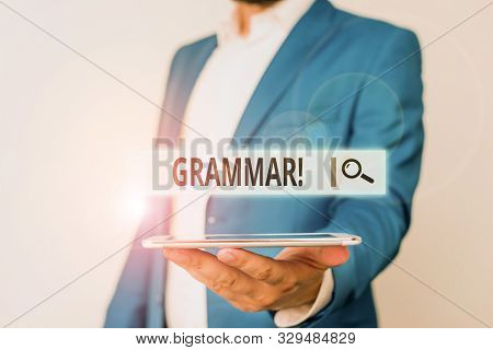Conceptual hand writing showing Grammar. Business photo showcasing whole system structure language syntax and morphology Man in blue suite and white shirt holds mobile phone in hand. stock photo