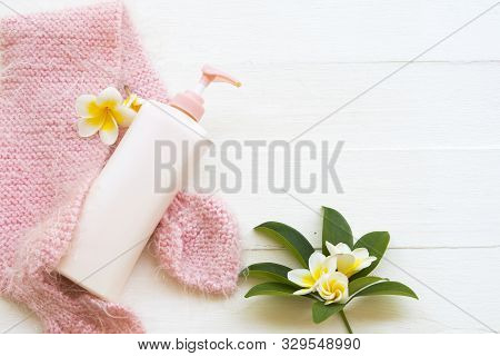 herbal cosmetics body lotion heath care for body skin with knitting wool scarf of lifestyle woman relax in winter season and flowers franigpani arrangement flat lay style on background wooden white stock photo