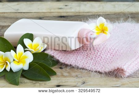 herbal cosmetics body lotion heath care for body skin with knitting wool scarf of lifestyle woman relax in winter season and flowers franigpani arrangement flat lay style on background wooden stock photo
