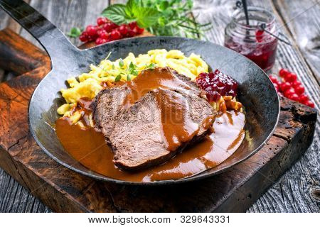 Traditional braised marinated German Sauerbraten from beef with spaetzle and cranberry jam in spicy brown sauce as closeup in a rustic wrought iron plate  stock photo