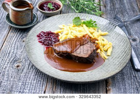 Traditional braised marinated German Sauerbraten from beef with spaetzle and cranberry jam in spicy brown sauce as closeup in a modern design plate  stock photo