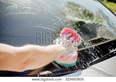 Male hand with tool for washing windows, car wash.man washing a soapy blue car with colorful sponge.Man washing car with a sponge and foam in the house yard.Manual car washing in car wash shop service. stock photo