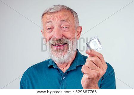 caucasian old senior man holding packed rubber latex condom in studio white background stock photo