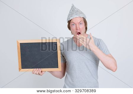 Young man with tin foil hat holding blackboard and looking shocked stock photo