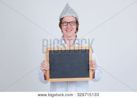 Happy young man doctor with tinfoil hat holding blackboard stock photo